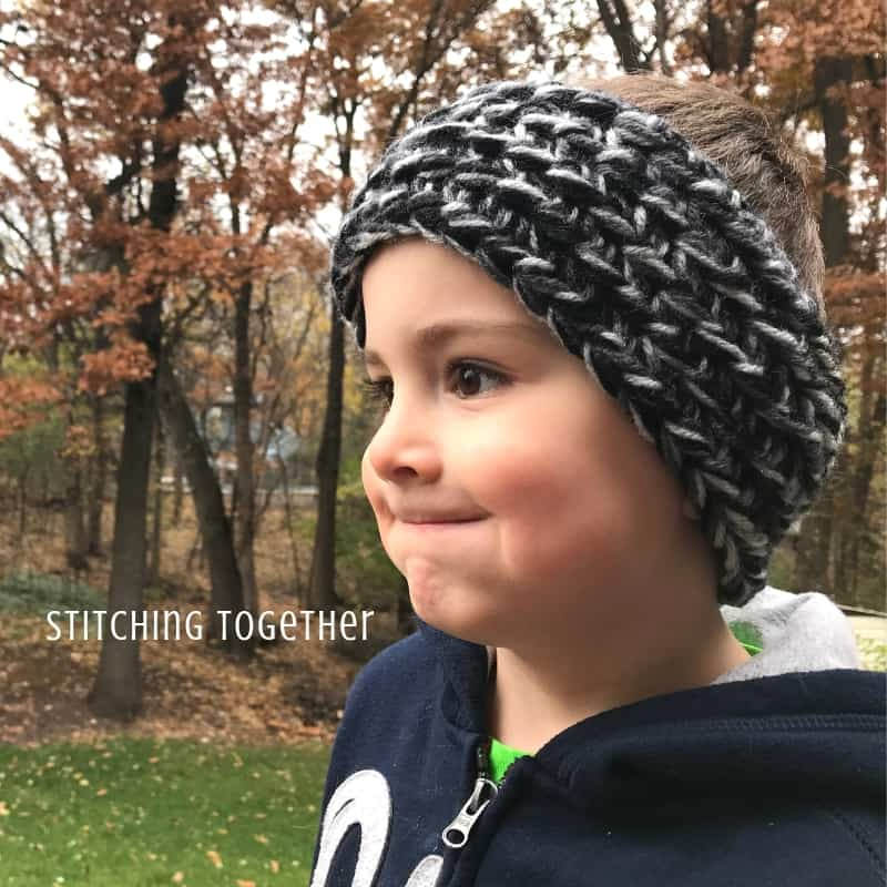 Child wearing a black and gray chunky crochet ear warmer