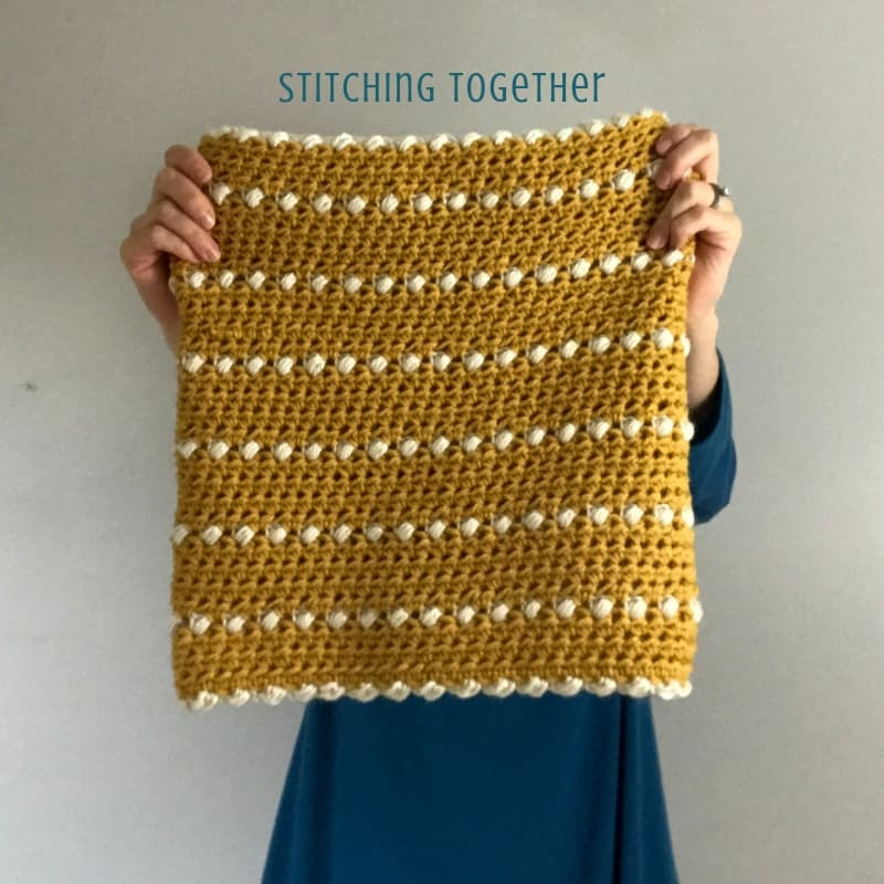 yellow and white crochet cowl being held up