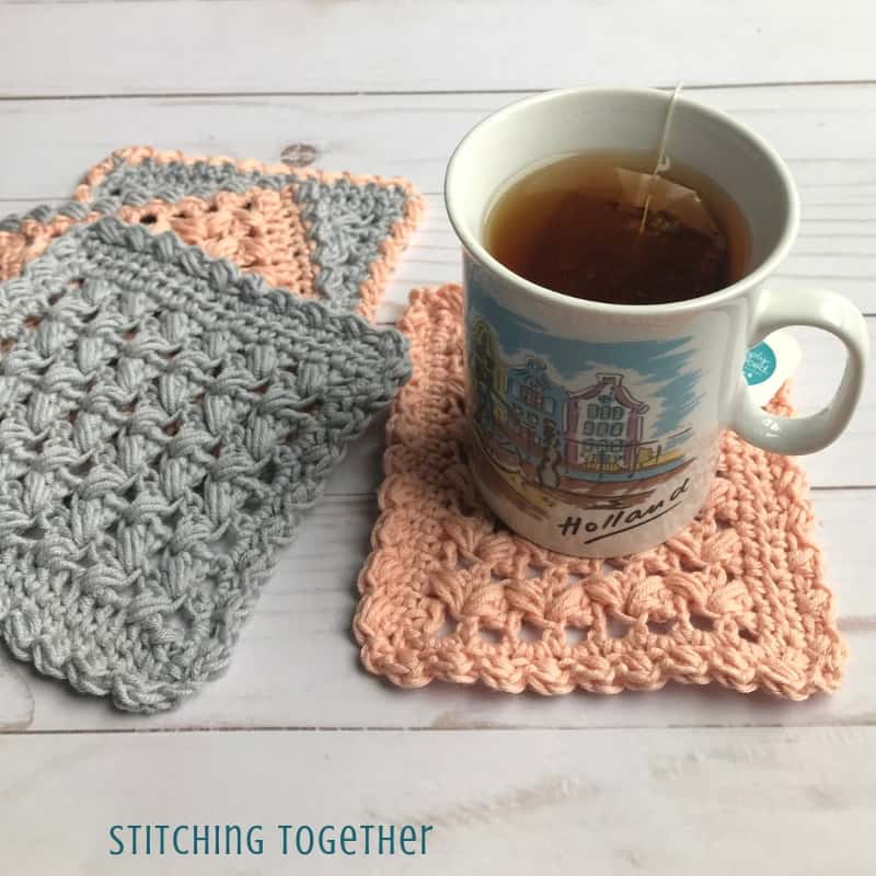 four pink and gray square crochet coasters and a cuppa