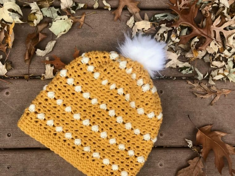 Mustard colored puff stitch crochet hat on ground surrounded by leaves