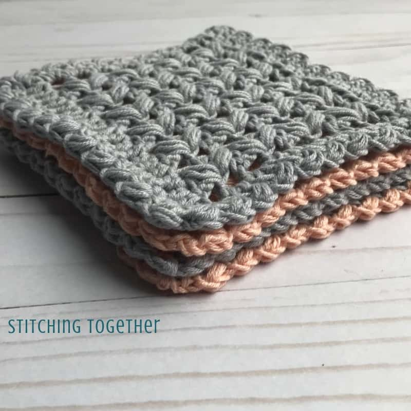 stack of pink and gray square crochet coasters