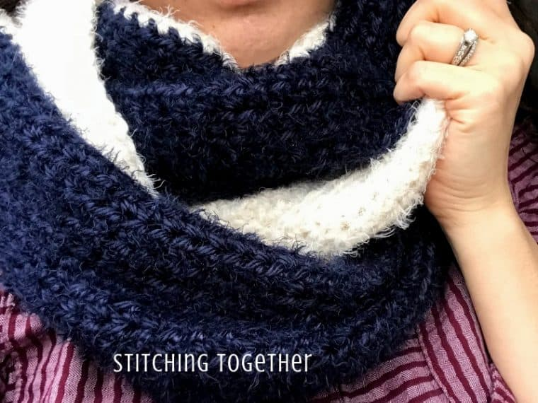 lady wearing luxury crochet infinity scarf that is blue and ivory