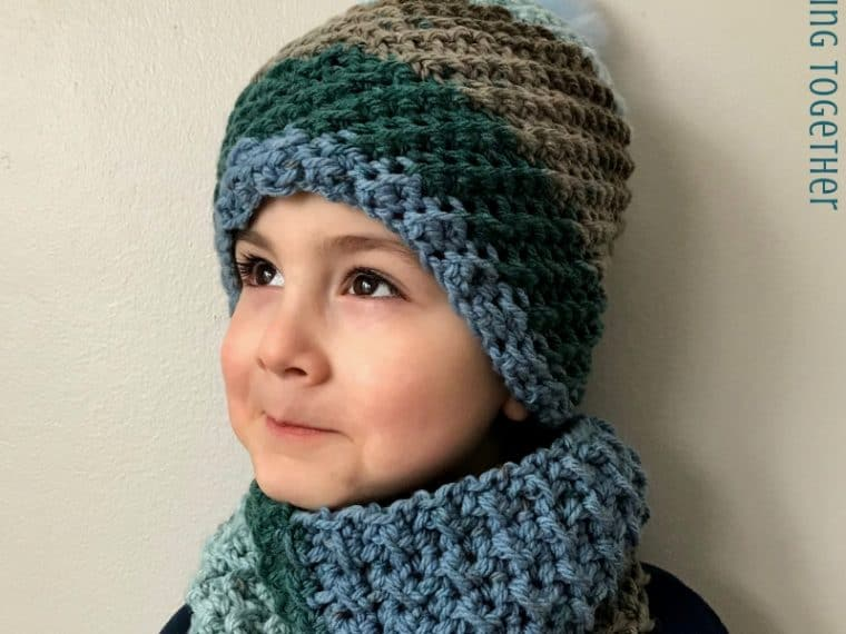 kid wearing blue and brown crochet hat and scarf