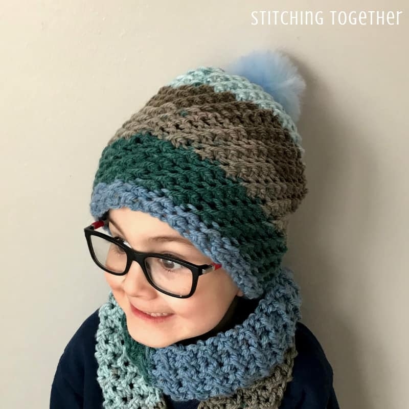 crochet hat and crochet boy scarf being worn by boy with glasses