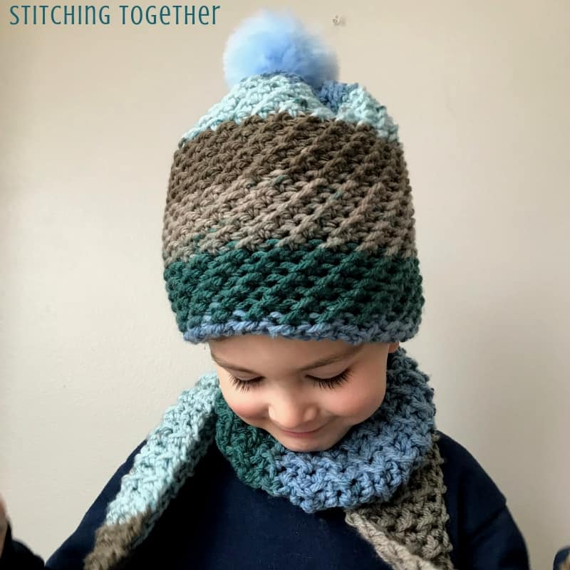 crochet hat with the crunch stitch and blue pom pom