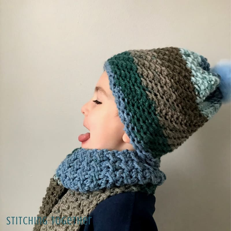 boy wearing crochet hat and scarf with his tongue out