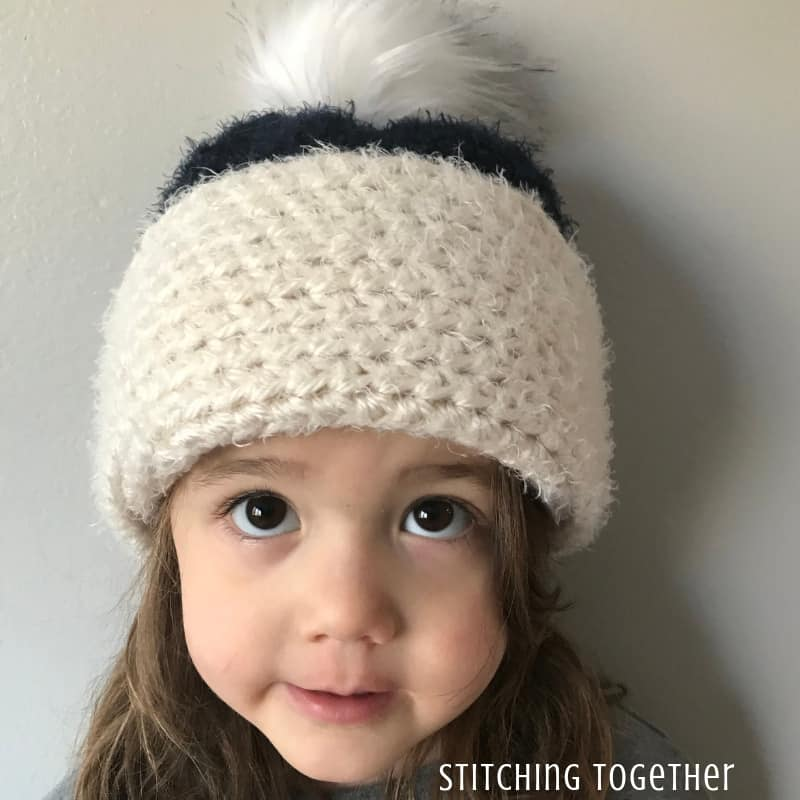 child with big brown eyes wearing a half double crochet hat