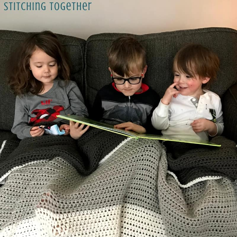 3 kids reading on a couch covered in a crochet blanket