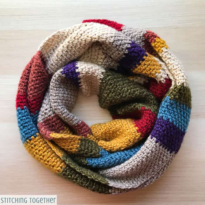 multicolored crochet scarf wrapped on ground