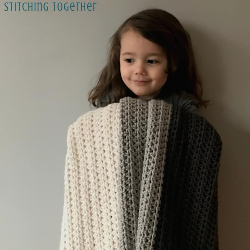 young girl holding gray striped half double crochet afghan