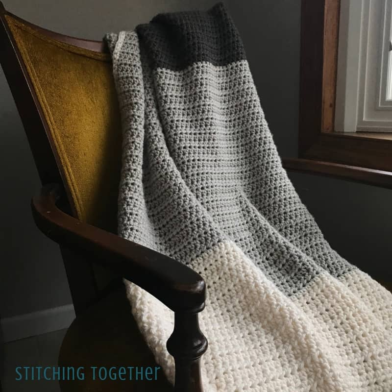 gray striped half double crochet blanket on yellow chair