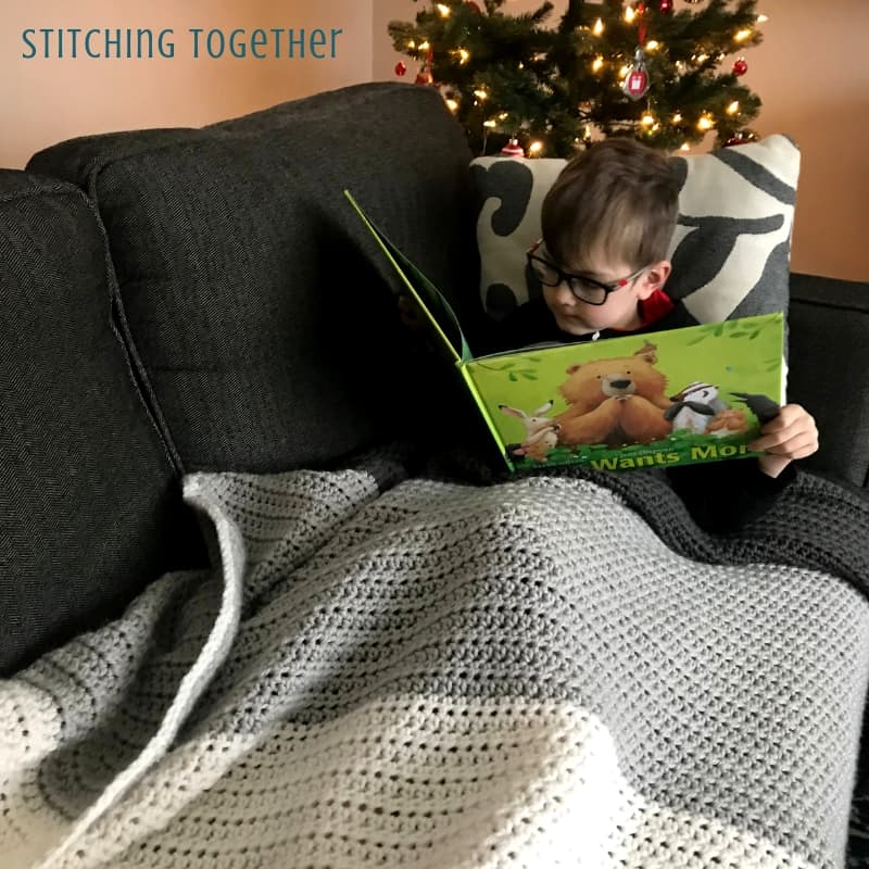 Boy reading on couch covered in a gray striped hdc blanket
