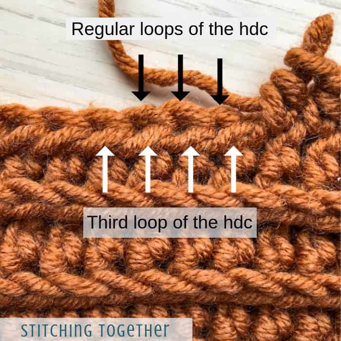 arrows showing the third loop of a half double crochet