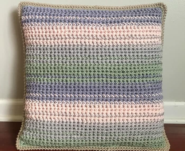 striped crochet throw pillow sitting on floor