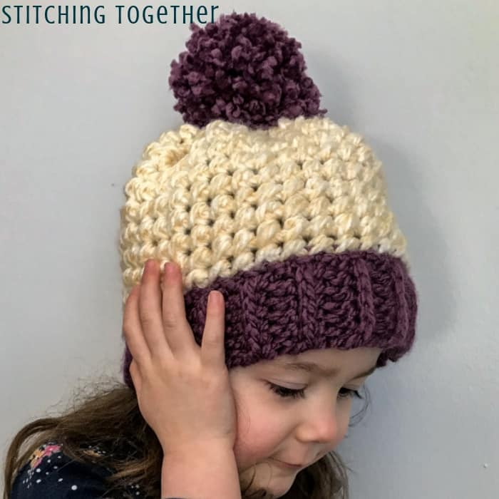 Kid in chunky crochet hat with pom pom