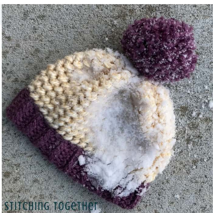 chunky crochet hat with pom pom and snow on it