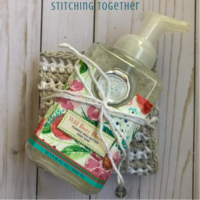 folded crochet dishcloth tied with a bottle of hand soap