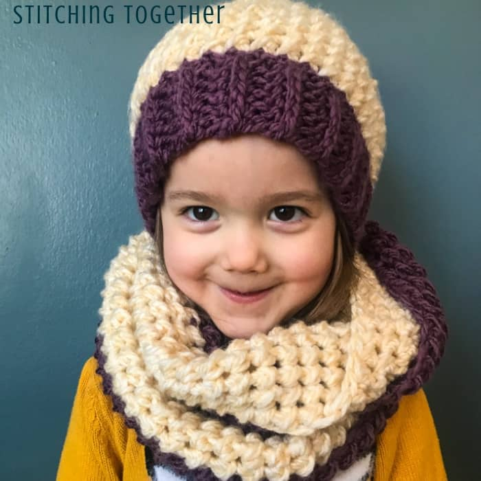 girl wearing purple and white crochet scarf and hat