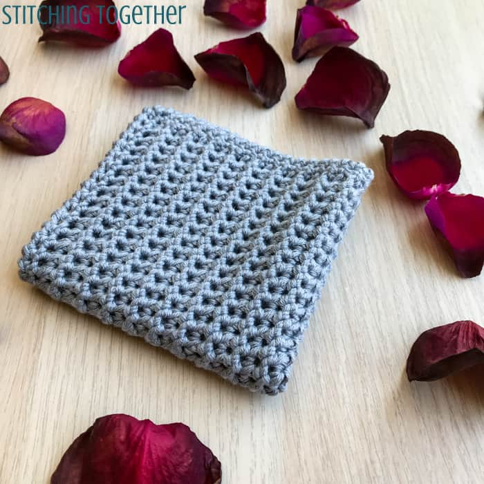 gray crochet washcloth surrounded by rose petals