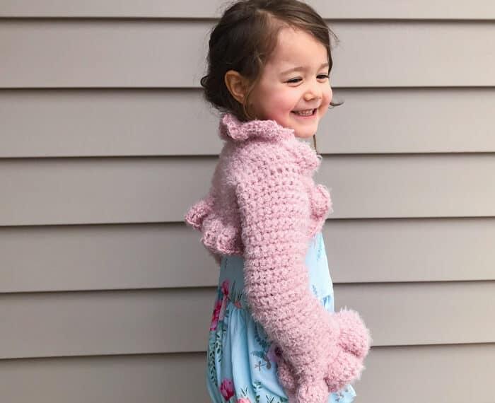 girl wearing pink crochet bolero with ruffles