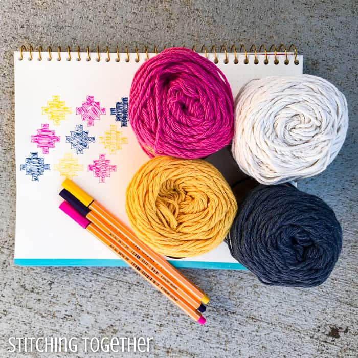 four balls of yarn, matching pens and a design drawn on graph paper
