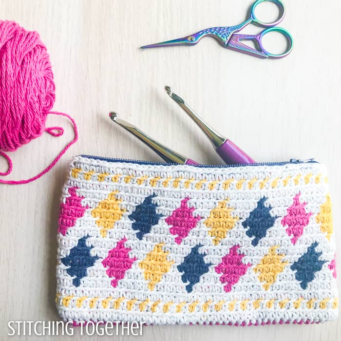 colorful crochet pouch with crochet hooks, yarn, and small scissors