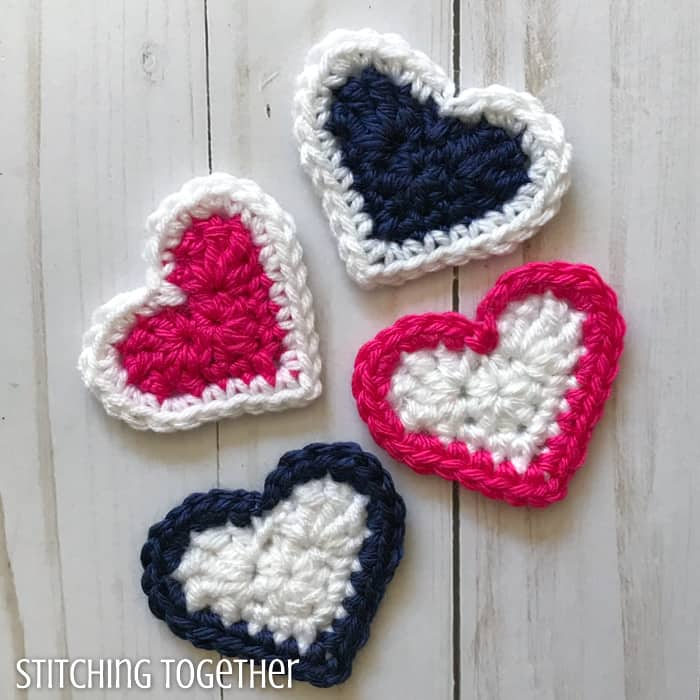 pink, white and blue crochet hearts laying on a wood background