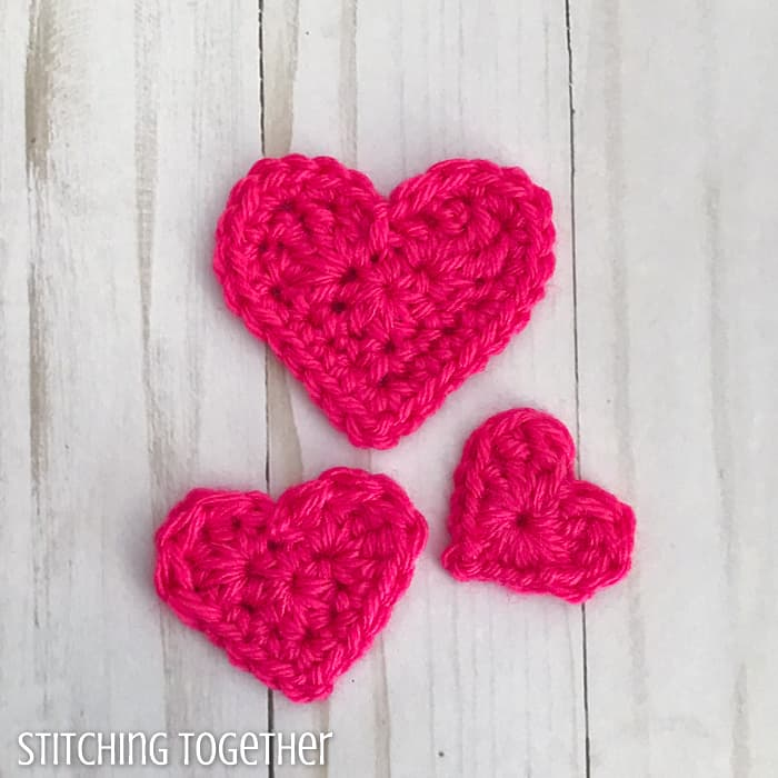 3 pink crochet hearts of different sizes