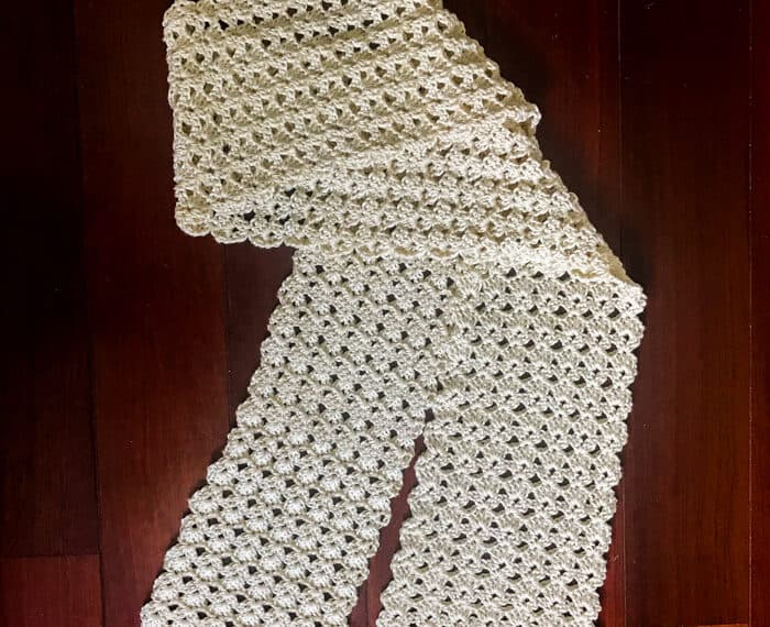shell stitch crochet scarf laid out and partially folded