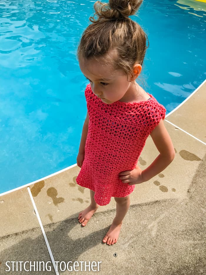 top view of a little girl in a pink crochet dress standing by a pool