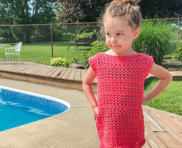 little girl wearing a pink crochet dress by a pool