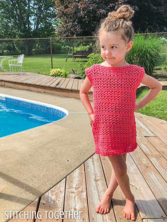 child wearing a pink crochet girl dress while standing by a pool