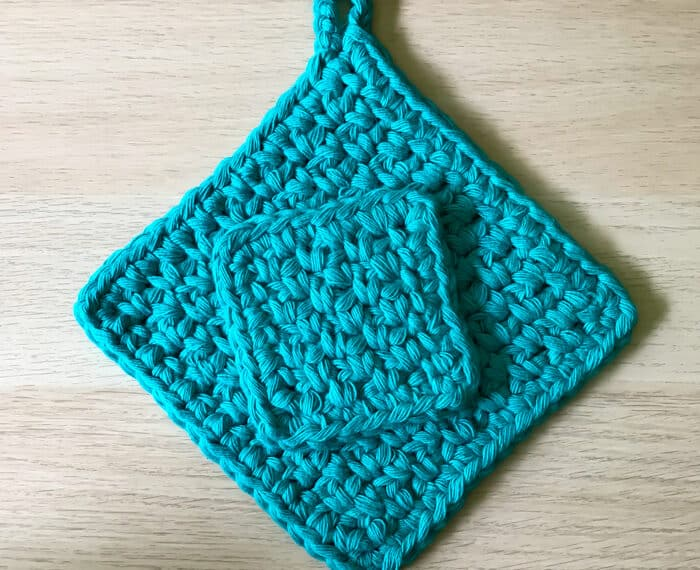 small crochet cloth sitting on top of a large crochet potholder