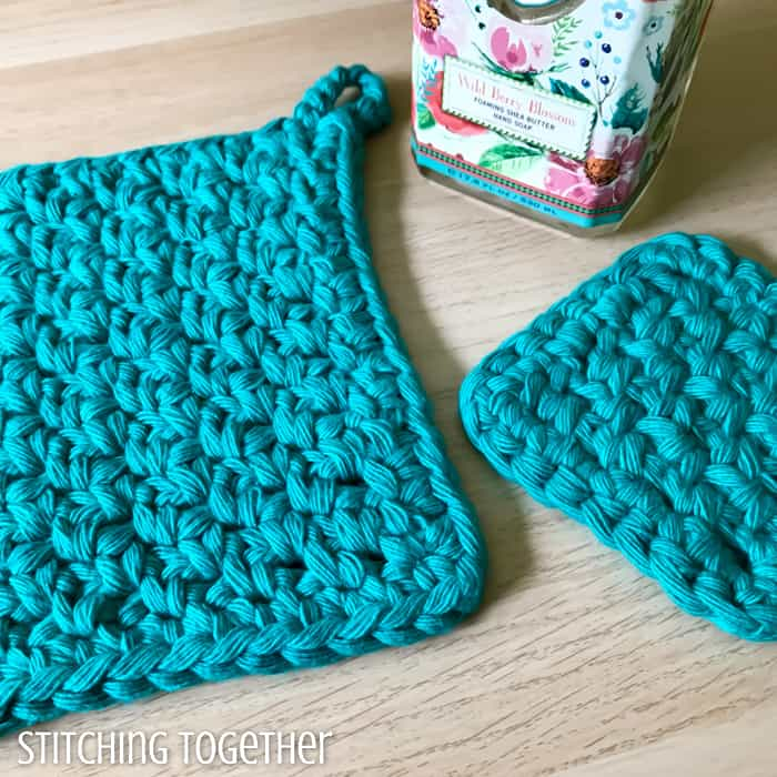 close up of crochet potholders done in the moss stitch and a soap bottle