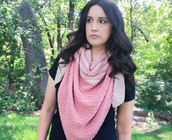 woman wearing a pink and tan striped crochet triangle scarf