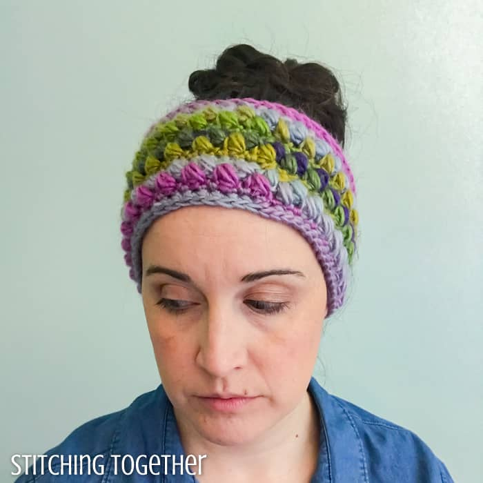 lady wearing a colorful crochet ear warmer with puff stitches