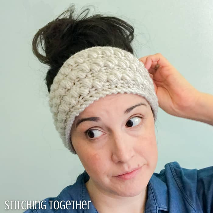 lady wearing a neutral puffy crocheted ear warmer