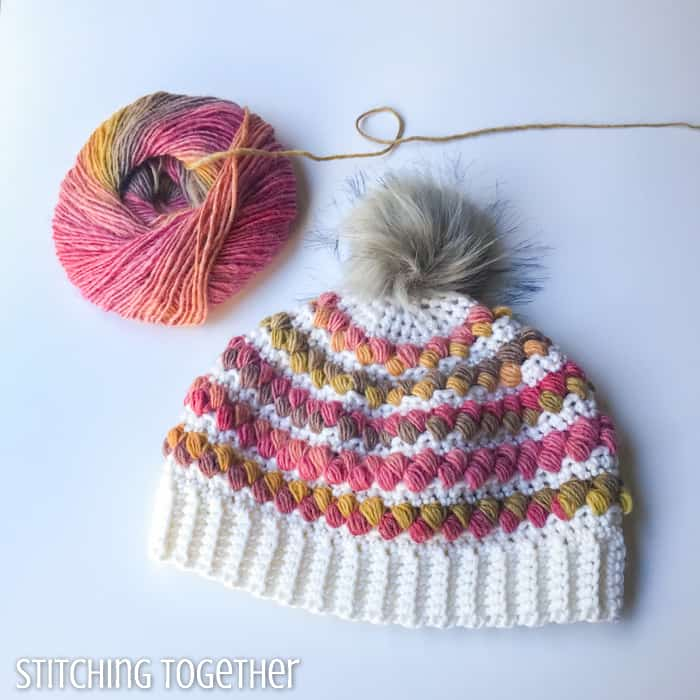 crochet hat for a women with colorful puff stitches and a ball of yarn sitting near