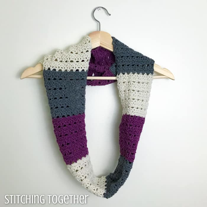 crochet infinity scarf hanging on a hanger
