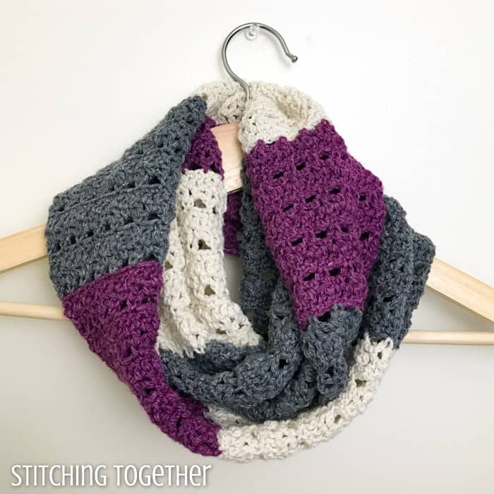 infinity scarf with stripes looped on a hanger