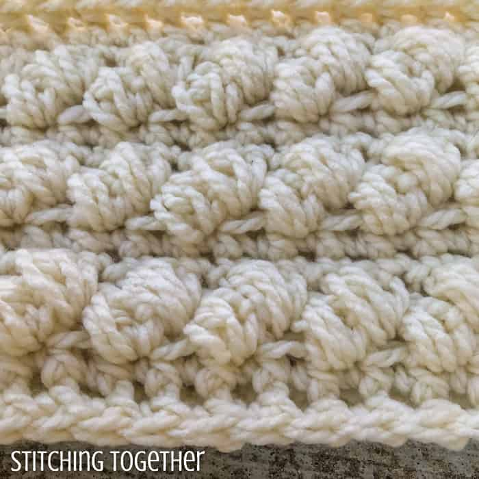close up of crochet puff stitches in a chunky scarf