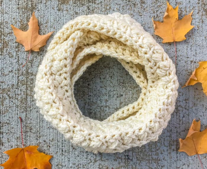 chunky crochet infinity scarf looped on the ground and surrounded by fall leaves