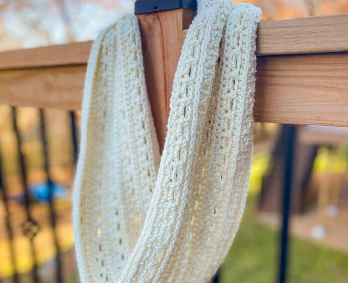 crochet infinity cowl hanging on a deck post