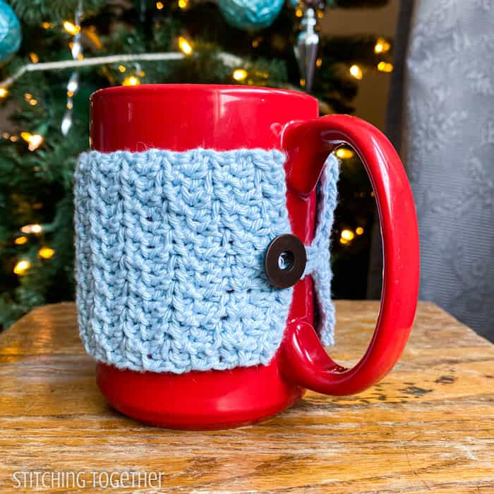 close up of crochet coffee mug cozy with button sitting on a down table
