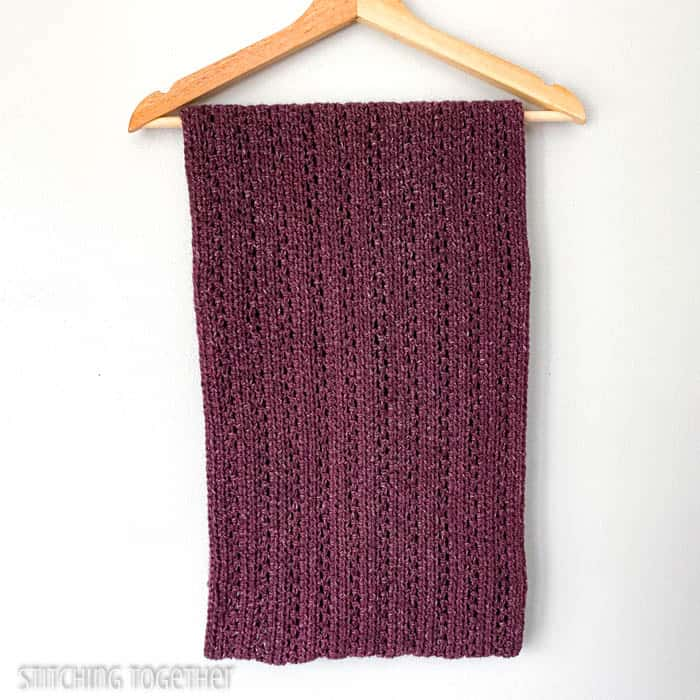 large burgundy infinity scarf folded and draped on a hanger