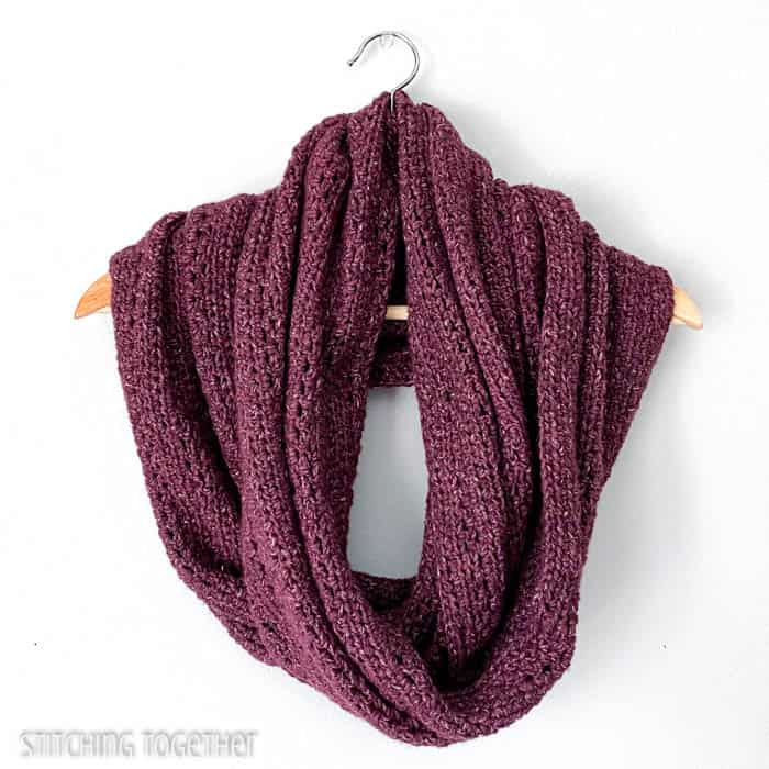 large burgundy infinity scarf wrapped on a hanger