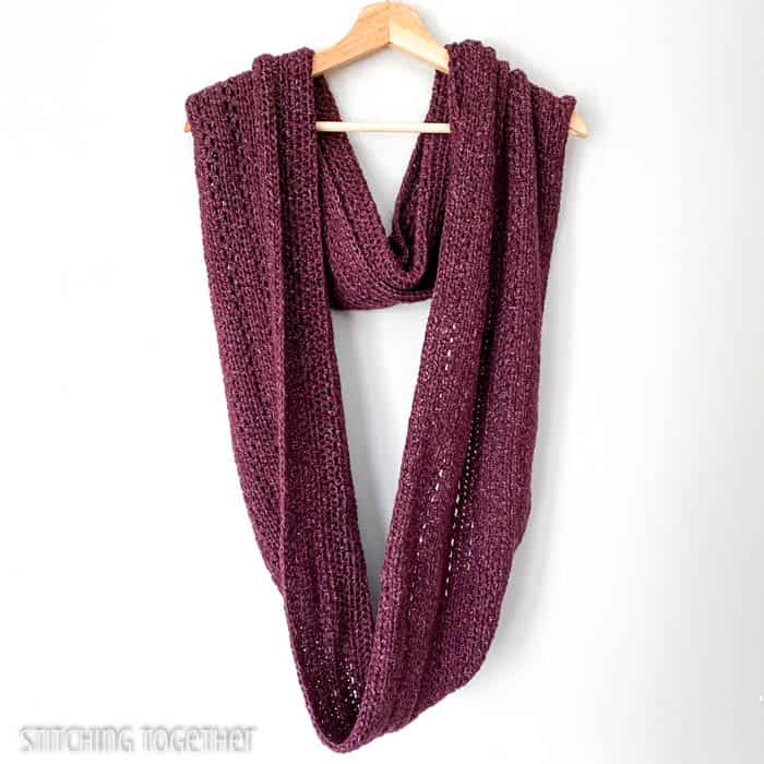oversized crochet infinity scarf draped on a hanger