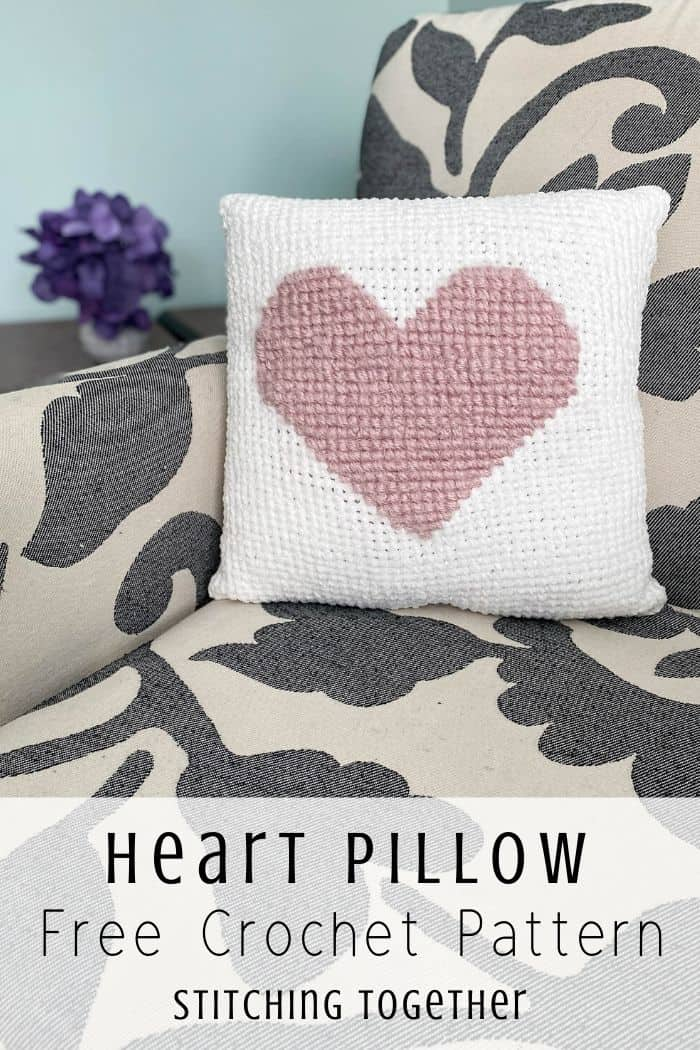 White crochet pillow with pink heart sitting on a chair