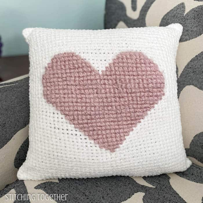 pink heart crochet pillow on white crochet fabric