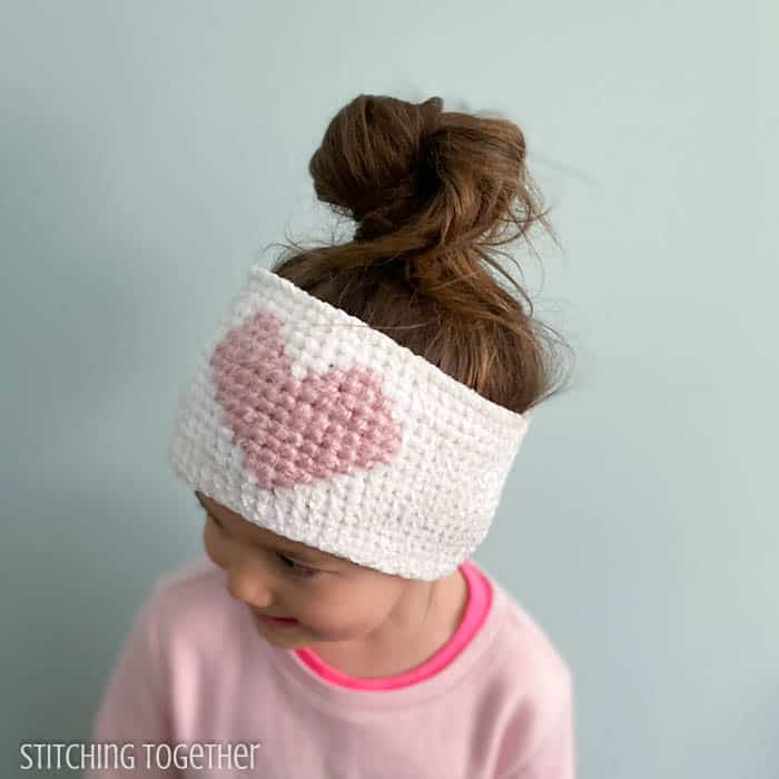 girl wearing a crochet heart ear warmer